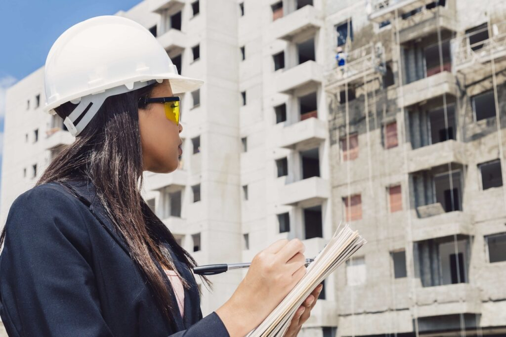 rsz_african-american-lady-safety-helmet-writing-notepad-near-building-construction